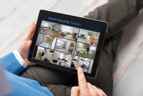 man-with-ipad-watching-his-home-security-cameras-while-away-from-home